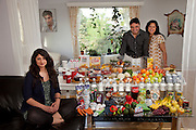 The Qureshi family of Lorenskog, Norway, an Oslo suburb. Pritpal Qureshi, 49, her husband Nasrullah, 51, and their daughter Nabeela, 23 with their typical week's worth of food in June. Their son, R. Shan, is studying at a distant university in Norway (photo on wall). Food Expenditure for one week: 2,002.48 Norwegian Kroner; $343.48 USD. Model-Released.