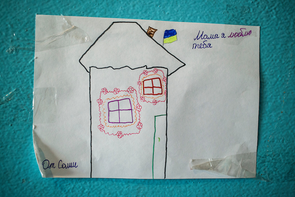 DNIPRODZERZHINSK, UKRAINE - OCTOBER 11: A child's drawing of a house with traditional designs and a Ukrainian flag hangs on the wall at the sports school where about 60 people displaced by fighting in Eastern Ukraine live on October 11, 2014 in Dniprodzerzhinsk, Ukraine. The United Nations has registered more than 360,000 people who have been forced to leave their homes due to fighting in the East, though the true number is believed to be much higher.(Photo by Brendan Hoffman/Getty Images) *** Local Caption *** ***