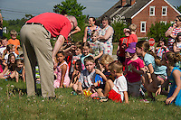 Gilford High School Tech Ed teacher Sean Walsh shows Gilford Elementary Kindergarten students Bryce Cook, Renee Henderson and Jaxen Lien an Estes Rocket following the launch as part of Stem Day on Wednesday morning.  (Karen Bobotas/for the Laconia Daily Sun)