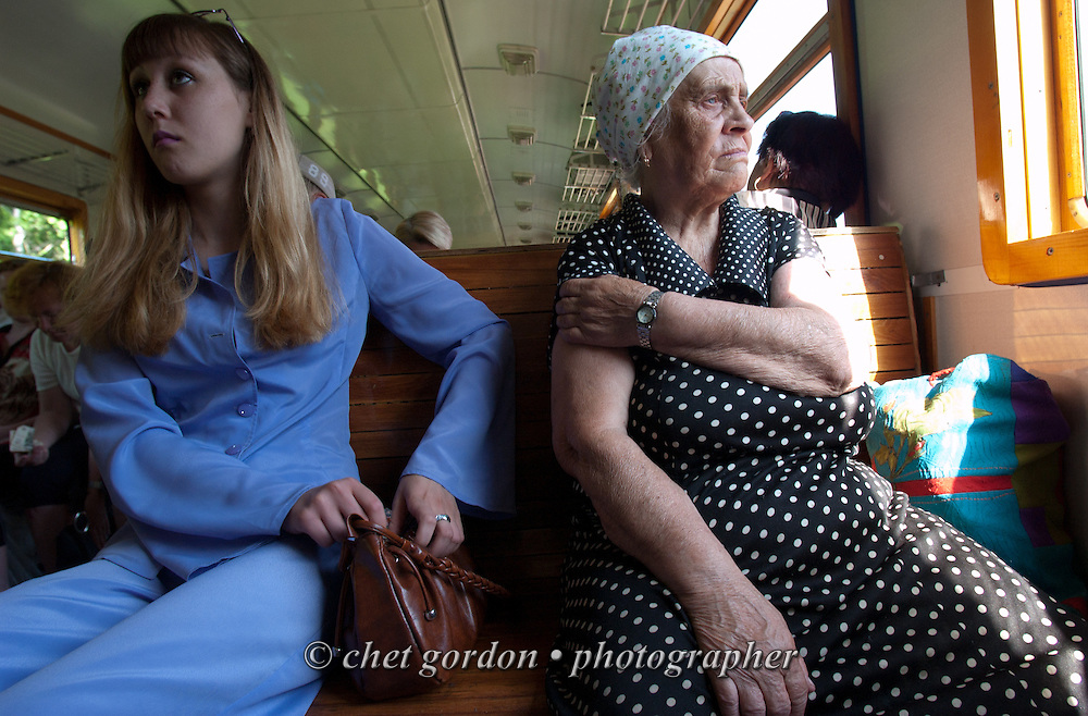 "A fashionable young Russian woman shares a seat with a ""babushka"" onboard an ""electricka"" or commuter train en route to Tiaga, Siberia Russian Federation on Monday, June, 13, 2005."