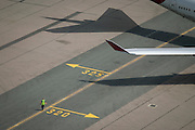 Aerial view (from control tower) of airport ramp marshal and airliner wing at London Heathrow airport. <br /> <br /> From the chapter entitled 'Up in the Air' and from the book 'Risk Wise: Nine Everyday Adventures' by Polly Morland (Allianz, The School of Life, Profile Books, 2015).