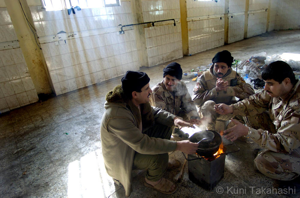 Iraqi soldiers cook breakfast at their barrack in Mosul, Feb 2005.