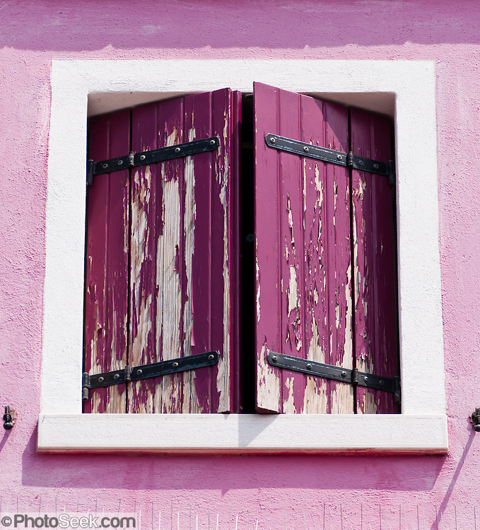 "Pink window shutters. Burano, known for knitted lacework, fishing, and colorfully painted houses, is a small archipelago of four islands linked by bridges in the Venetian Lagoon, northern Italy, Europe. Burano's traditional house colors are strictly regulated by government. The Romans may have been first to settle Burano. Romantic Venice (Venezia), ""City of Canals,"" stretches across 117 small islands in the marshy Venetian Lagoon along the Adriatic Sea in northeast Italy, between the mouths of the Po (south) and Piave (north) Rivers. Venice and the Venetian Lagoons are on the prestigious UNESCO World Heritage List."