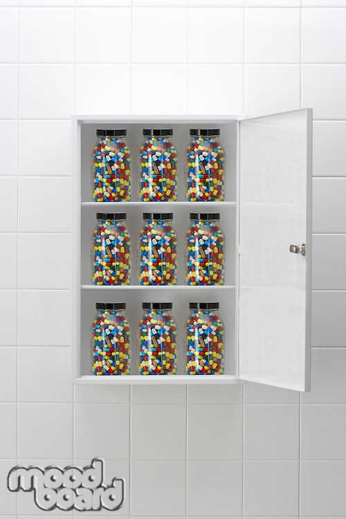 Jars of pills in bathroom cabinet