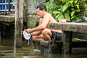 "17 NOVEMBER 2012 - BANGKOK, THAILAND:  A man does his dishes in the waters of a khlong or canal in the Thonburi section of Bangkok. Bangkok used to be known as the ""Venice of the East"" because of the number of waterways the criss crossed the city. Now most of the waterways have been filled in but boats and ships still play an important role in daily life in Bangkok. Thousands of people commute to work daily on the Chao Phraya Express Boats and fast boats that ply Khlong Saen Saeb or use boats to get around on the canals on the Thonburi side of the river. Boats are used to haul commodities through the city to deep water ports for export.    PHOTO BY JACK KURTZ"