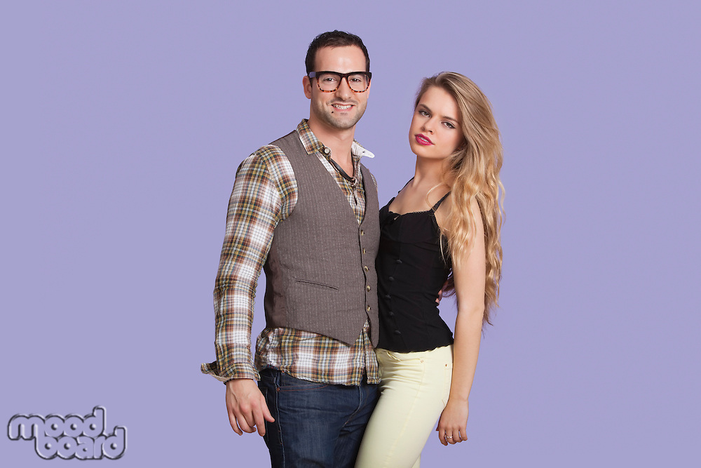 Portrait of young couple against purple background