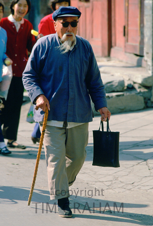 Old man walking with a stick in Beijing in China