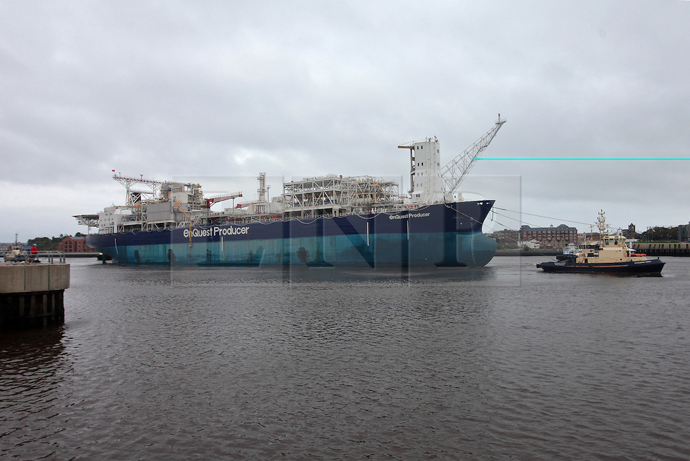 "Licensed to London News Pictures. 18/10/2013. North Tyneside, UK, In another milestone for the improving fortunes of the River Tyne's offshore industrial base, Enquest Producer, a 248m, 92,000tonne Floating Production Storage Offshore (FPSO) unit is the largest vessel to arrive on the Tyne for 10 years. She has been towed from Hamburg to Wallsend-based OGN for commissioning before being placed in Enquest's Alma/Galia development which is revitalising the Argyll oilfield. The work on the Tyne is expected to take 8 months and has created a number of jobs. <br /> <br /> The vessel arrived under tow and without engines making it a challenging job for the Port of Tyne's team of <br /> Pilots.<br /> <br /> Captain Mike Nicholson, Port of Tyne Harbour Master, said: ""We have developed a good level of experience in <br /> handling FPSO's but working with a 'dead ship' with no power always requires careful planning.<br /> ""Conditions have to be just right, the weather will be critical, we will need winds of force 4 or less with <br /> benign sea and swell. Three of our most senior Pilots will be employed to coordinate five tugs with a total <br /> pulling force of over 400 tonnes.""<br /> <br /> Seven oil production wells and two water injection wells will be feeding crude to the EnQuest Producer, <br /> capable of processing 57,000 barrels per day and storing 625,000 barrels (almost 100 million litres) of <br /> crude oil. EnQuest Producer has been undergoing major modification and life extension work at theHamburg <br /> shipyard of Blohm and Voss before being moved to the Tyne for completion. <br /> <br /> Enquest Producer will be Located in the central North Sea, 310km south-east of Aberdeen, in water depth of <br /> approximately 80m.<br /> <br /> Argyll was first discovered in 1971 and four years later was the first North Sea field to produce oil, <br /> before being decommissioned twice over the subsequent decades.      <br /> <br /> Photo credit: Adrian Don/LNP"