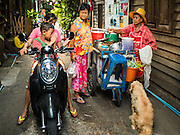 07 APRIL 2016 - BANGKOK, THAILAND: A woman and her son drive their motorbike past a curry vendor in the squatters' community behind the walls in Mahakan Fort. Mahakan Fort was built in 1783 during the reign of Siamese King Rama I. It was one of 14 fortresses designed to protect Bangkok from foreign invaders, and only of two remaining, the others have been torn down. A community developed in the fort when people started building houses and moving into it during the reign of King Rama V (1868-1910). The land was expropriated by Bangkok city government in 1992, but the people living in the fort refused to move. In 2004 courts ruled against the residents and said the city could take the land. The final eviction notices were posted last week and the residents given until April 30 to move out. After that their homes, some of which are nearly 200 years old, will be destroyed.       PHOTO BY JACK KURTZ