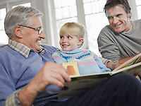 Grandfather reading to girl (3-4) father looking on in house
