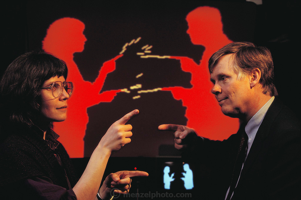 Myron Kruger and his assistant, Katrin Hinrichsen, 'shooting' at each other with computer-generated sparks. Kruger is a pioneer of artificial reality, a method allowing people to interface directly with computers. In Kruger's method, called VideoPlace, the participants stand in front of a backlit screen. A video camera forms an image of their silhouette; the computer is programmed to respond to particular actions in a particular way. Here the computer sees the operators pointing, and interprets this as fire a spark in this direction. The computer-generated image appears in the background here on a large video screen. Model Released (1990)