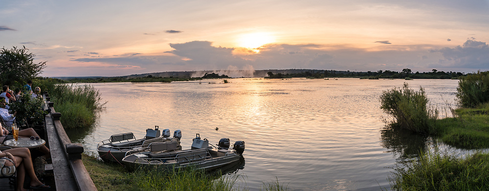 View from the sundeck of the Royal Livingstone Hotel of the the Zambezi River as the sun sets over the water in Livingstone, Zambia