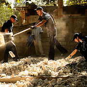 100129-N-5345W-096.GRAND GOAVE, Haiti (Jan. 29, 2010) .Gunner's Mate 3rd Class Peter Sansone, center, tosses aside a scoop of rubble as Fireman Travis Sawicki and Boatswain's Mate 3rd Class Isabel Pericon sift through debris as Sailors from the multi-purpose amphibious assault ship USS Bataan (LHD 5) work to clean up an outdoor classroom at the Lifeline Christian Ministries Mission in Grand Goave, Haiti. Bataan and the amphibious dock landing ships USS Fort McHenry (LSD 43), USS Gunston Hall (LSD 44) and USS Carter Hall (LSD 50) are participating in Operation Unified Response as the Bataan Amphibious Relief Mission by providing military support capabilities to civil authorities to help stabilize and improve the situation in Haiti. (U.S. Navy photo by Mass Communication Specialist 2nd Class Kristopher Wilson/RELEASED)