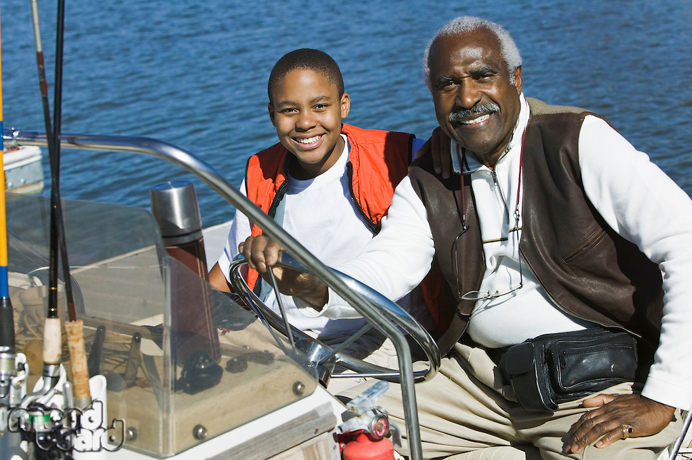 Grandfather Taking Grandson Fishing in Boat