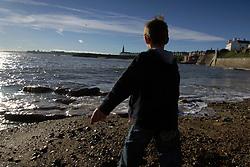 Boy on Cullercoats beach; NE England
