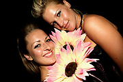 Two sexy girls holding flowers at Manumission pre party, Ibiza, 2006