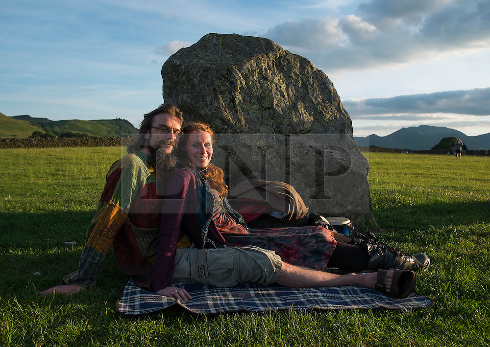 © Licensed to London News Pictures. <br /> 20/06/2014. <br /> <br /> Castlerigg Stone circle, Cumbria, England<br /> <br /> A couple sit at the ancient site of Castlerigg Stone Circle near Keswick in Cumbria and watch the sunset on the evening of the Summer Solstice.<br /> <br /> Photo credit : Ian Forsyth/LNP