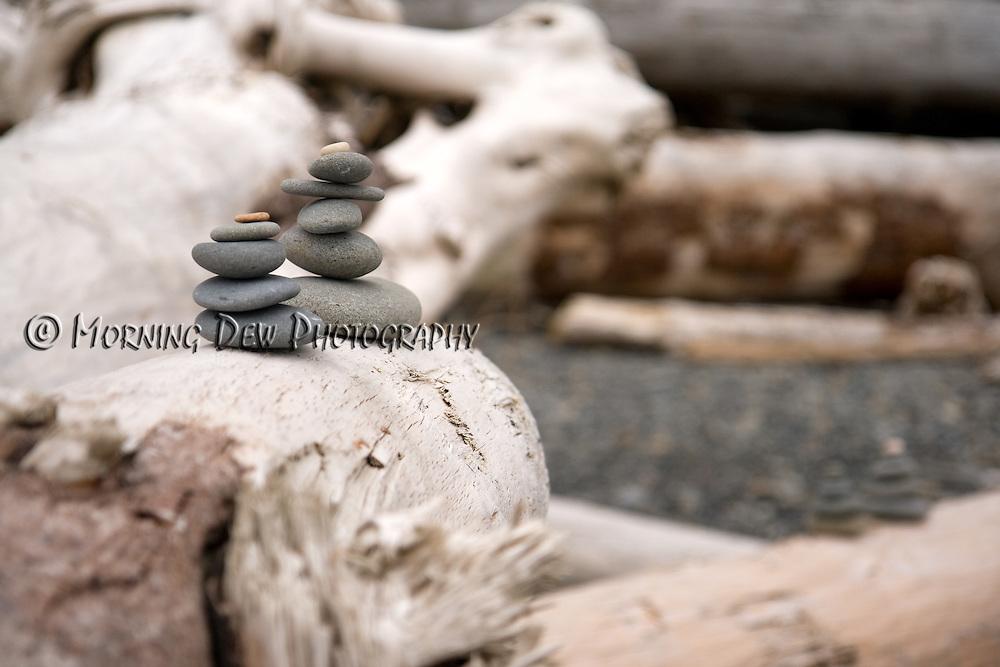 Beach stones are stacked upon driftwood at Rialto Beach, Washington.