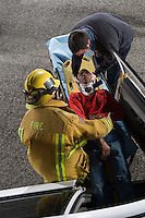 Firefighter and paramedic rescuing car accident victim