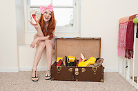 Portrait of young woman sitting near window showing high heels with suitcase full of footwear