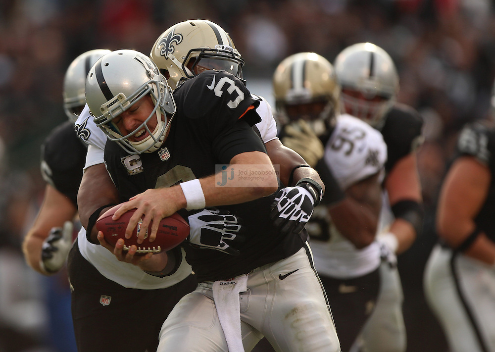 Oakland Raiders quarterback Carson Palmer (3) is sacked by New Orleans Saints defensive end Will Smith (91) during an NFL game on Sunday, Nov. 18, 2012 at the Oakland Coliseum in Oakland, Ca. (AP Photo/Jed Jacobsohn)