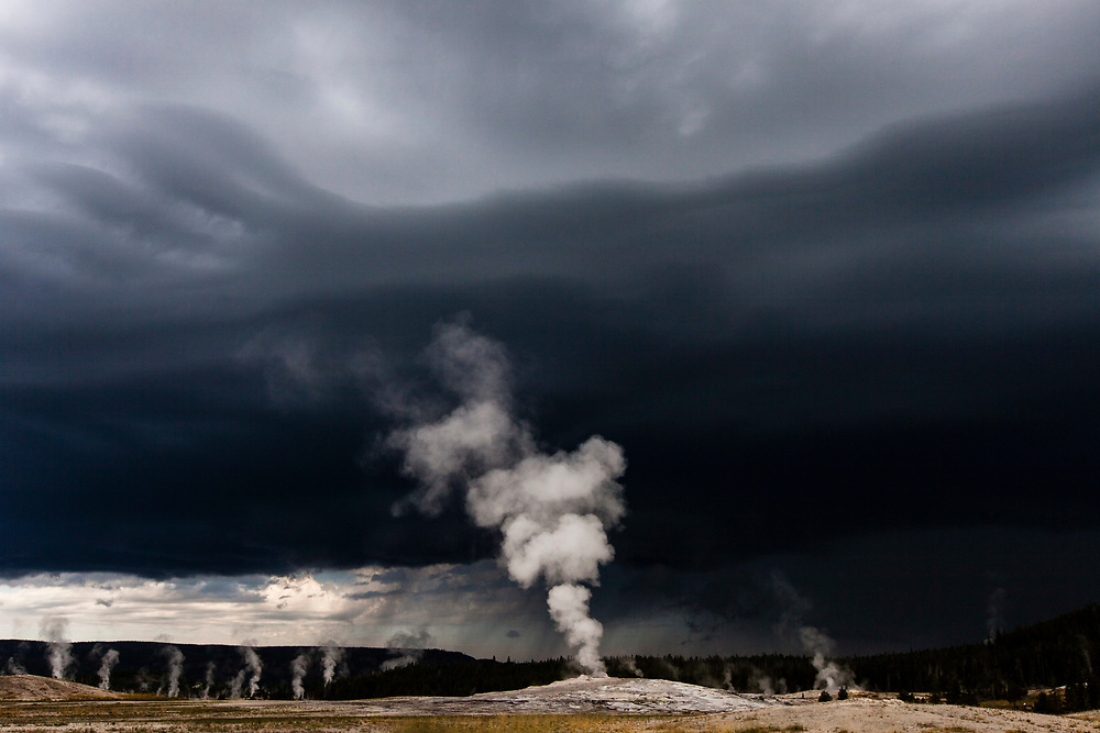 People watch as Old Faithful Geyser erupts, Yellowstone National Park, Wyoming, United States