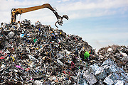 Grab machine organising metal recycling of scrap metal to avoid environmental pollution in England