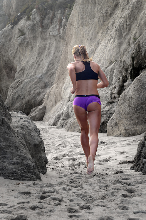 Female athlete in purple shorts runs barefoot at El Matador Beach in Malibu, CA. Los Angeles Fitness Photographer - Fitness Photographers