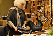 Canada, Ontario Windsor, 2016. Artist Trading Card workshop at Ten Thousand Villages is a MayWorks Windsor 2016 event. Susan Gold, left, speaks with Kathleen Cant about artist trading cards.