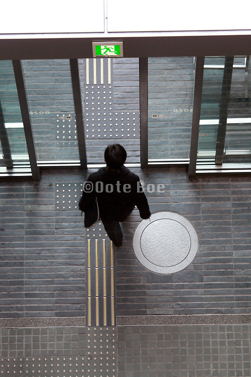 overhead view of young businessman leaving office building