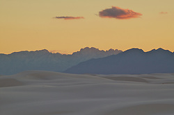 The white dunes of White Sands National Monument in New Mexico look like a turbulent sea of white below the sunset.