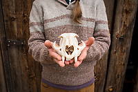 Young woman holding a mountain lion scull. Aravaipa Canyon Preserve, AZ.