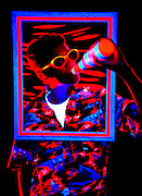 Young boy with glowing shirt, bottle and frame.Black light