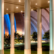 View of Kauffman Center for the Performing Arts through columns of Kansas City Convention Center Ballroom entrance. Kauffman Center lit in Royal Blue lighting for the 2015 KC Royals MLB World Series.