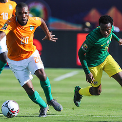 24 June 2019, Egypt, Cairo: Ivory coast's Serey Die and South Africa's Percy Tau in action during the 2019 Africa Cup of Nations Group D soccer match between South Africa and Ivory coast at Al-Salam Stadium. <br /> Photo : PictureAlliance / Icon Sport
