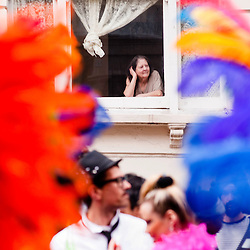 London, UK - 27 August 2012: a resident watches the Notting Hill Carnival parade from the window of her home.