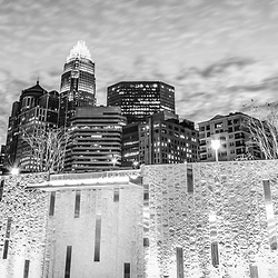 Charlotte skyline at night black and white panorama photo with Romare Bearden Park waterfall fountain and downtown Charlotte cityscape against a cloudy sky. Charlotte, North Carolina is a major city in the Eastern USA.
