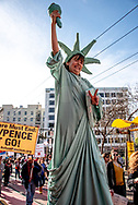 San Francisco, USA. 19th January, 2019. A woman dressed as the Statue of Libery walks on stilts down Market Street and flashes the peace sign in the Women's March San Francisco. Credit: Shelly Rivoli/Alamy Live News