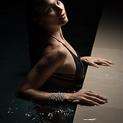 Portrait of young beautiful woman in swimming pool at night.