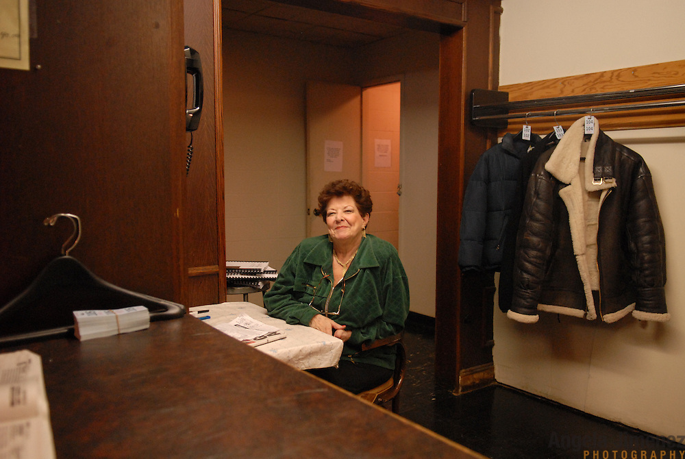 Mary Caruso, who has been working at the Aqueduct racetrack in New York City for 19 years, works a coat check outside the Man O' War bar on February 16, 2007. The coat trade is often slow: and she gets better business with the Aqueduct and off-site tip sheets she sells for $25 and $40, respectively. She bases her bets, which she places on most races, on her favorite jockeys, owners and trainers or the lineage of the horse...Betting on the horses is still a popular game and the money still flows, but off track betting and other forms of entertainment have eroded live attendance at the races.  The daily diehard betters and horse lovers who sparsely populate the place on work days are joined by a bigger crowd on the weekends. ..The Aqueduct, located in Ozone Park, Queens, is the only horse racing track in New York City and probably the coldest in the country (most of the others are in Kentucky, Florida or California). Horses race on the winterized inner dirt rack from January 1st through the end of April. Aqueduct was built in 1894, renovated in 1959, then opened for winter racing in 1975. It is the winter race track operated by the New York Racing Association (NYRA), which also runs Belmont and Saratoga in the warm seasons. Betters at Aqueduct watch and bet on the nine daily live races and all other races around the country via Simulcast. ..