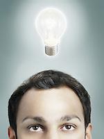 Illuminated lightbulb over man's head high section studio shot