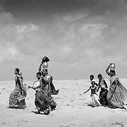 Sri Lanka. The village women dress in their finest sari's for this festival. In the background, are women cooking food as an offering at the temple. Festival at the Hindu Kali Kovil in Udappu. West Coast.