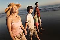 Family walking on beach at dusk