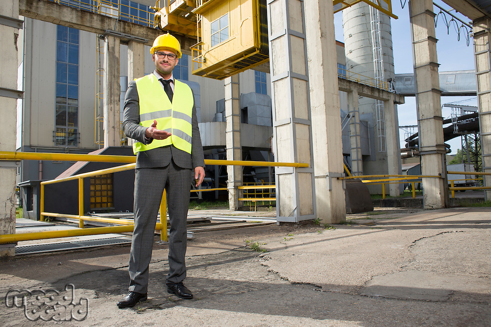 Full length portrait of confident male engineer gesturing outside industry