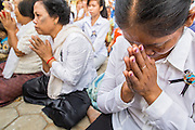 "01 FEBRUARY 2013 - PHNOM PENH, CAMBODIA:  A mourner prays as the King's funeral procession passes her in Phnom Penh. Norodom Sihanouk (31 October 1922 - 15 October 2012) was the King of Cambodia from 1941 to 1955 and again from 1993 to 2004. He was the effective ruler of Cambodia from 1953 to 1970. After his second abdication in 2004, he was given the honorific of ""The King-Father of Cambodia."" Sihanouk died in Beijing, China, where he was receiving medical care, on Oct. 15, 2012. His cremation is will be on Feb. 4, 2013. Over a million people are expected to attend the service.   PHOTO BY JACK KURTZ"