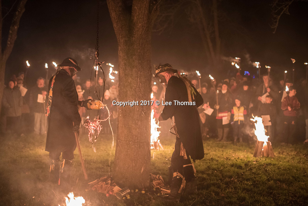 Much Marcle, Herefordshire, UK. 6th January 2018. Pictured: Morris men perform a ritual where cider is poured around the base of a apple tree, the base of which is strewn with apples and toast.  / Hundreds of people both young and old gathered at the Westons Cider Mill and adjoining orchard to take part in the traditional Wassail ceremony. The event at Much Marcle in Herefordshire was attended by the Silurian morris side who entertained the crowd with witty repartee, raucous dancing and music. According to their website, the true origins of blackened faces are lost to history, but are widely believed to be simply a form of disguise, possibly to overcome the oppressive anti-begging laws of the 17th century, and the eternal embarrassment of being a morris man. The orchard-visiting wassail refers to the ancient custom of visiting orchards in cider-producing regions of England, reciting incantations and singing to the trees to promote a good harvest for the coming year  // Lee Thomas, Tel. 07784142973. Email: leepthomas@gmail.com  www.leept.co.uk (0000635435)