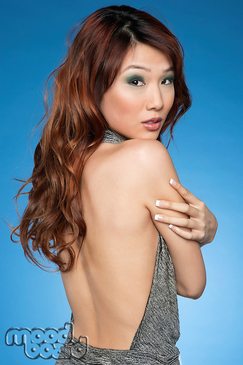 Beautiful Chinese brunette looking back over colored background
