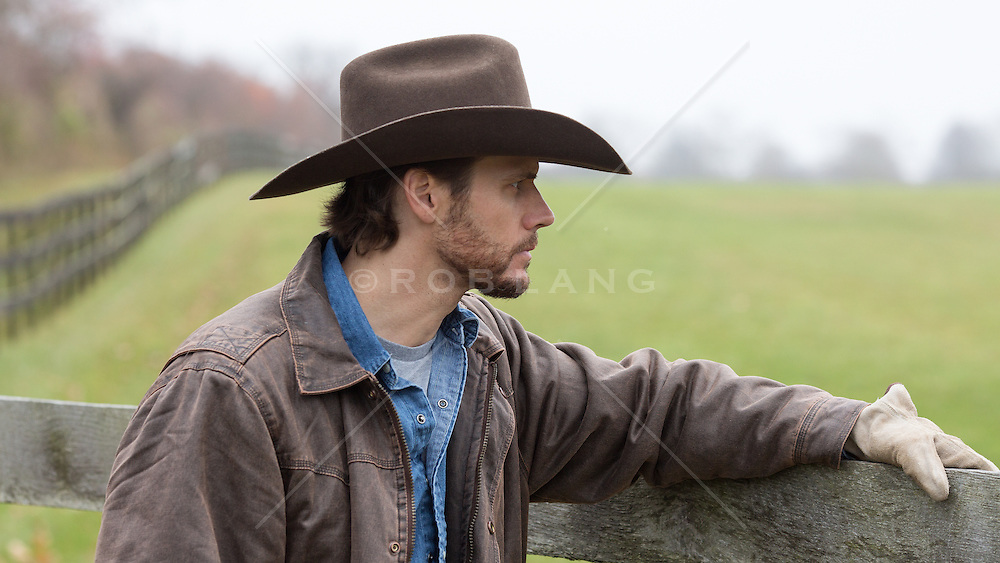 rugged good looking cowboy outdoors on a ranch leaning on a wooden fence