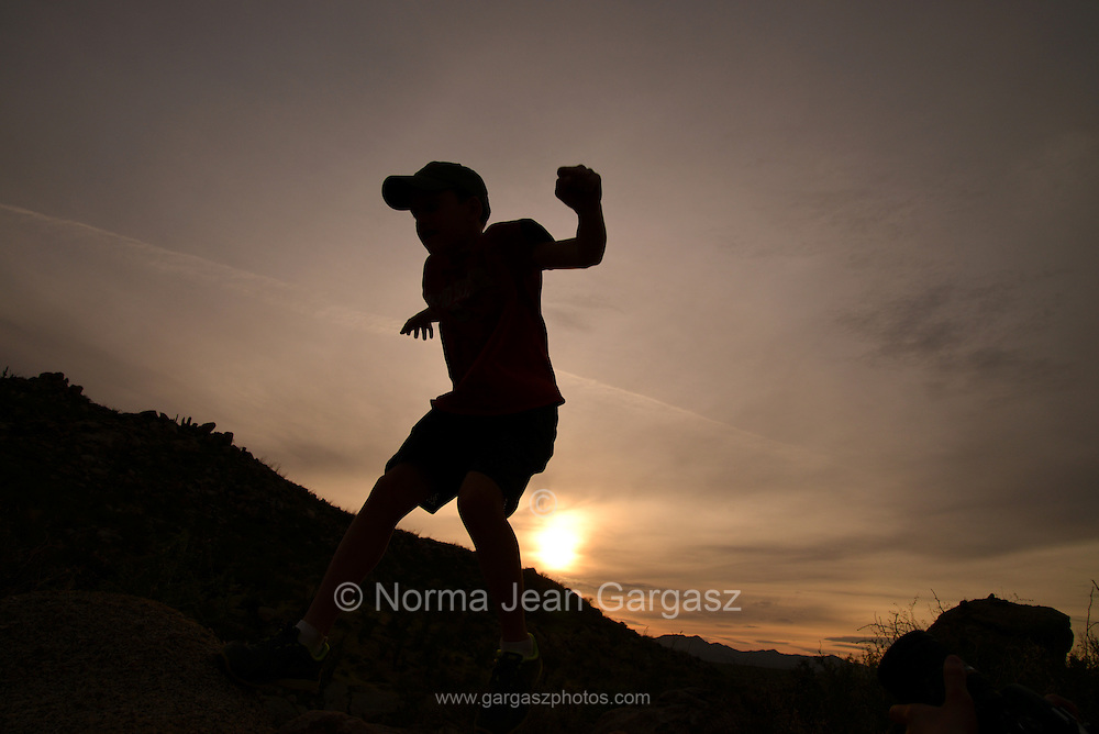 Boys jump boulders while hiking in the foothills of the Santa Catalina Mountains, Sonoran Desert, Catalina, Arizona, USA.