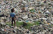 Port-au-Prince, Haiti.<br />A young boy picks his way through a garbage strewn area of Cite Soleil, the often violent pro-Aristide slum.  Life here is run by gangs, and a no-go area for the Haitian police. Many homes have been destroyed in gang violence, and the absence of municipal authorities sees garbage strewn in the area. Haiti, the western hemisphere's poorest country, faces another election.